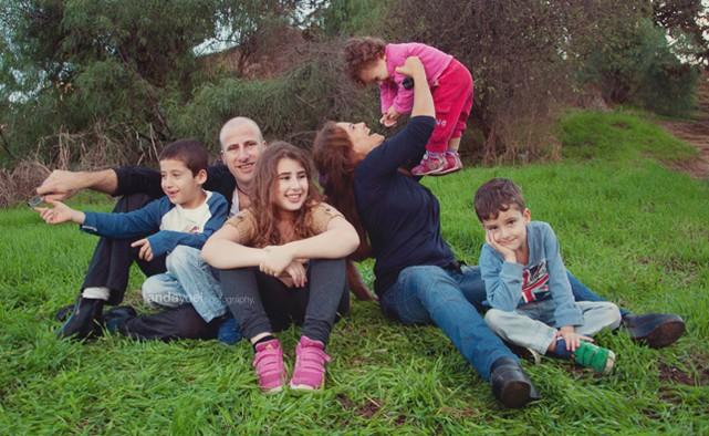 אמא מרימה תינוקת ומחייכת אליה יחד עם האחים והאבא מסדרת צילומי משפחה בטבע