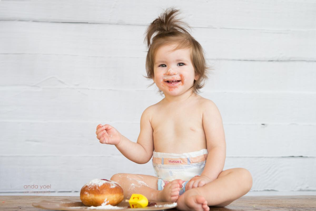 צילום תינוק חייכן עם סביבון וסופגניה בחנוכה - אנדה יואל