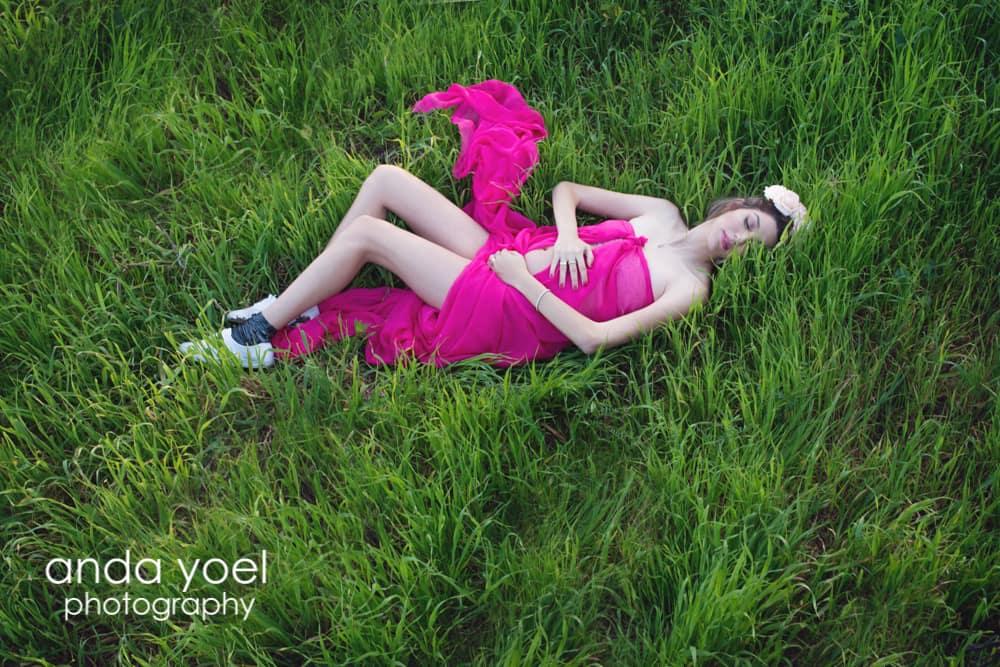 הריונית בשמלה סגולה שוכבת על דשא בסשן צילומי הריון בטבע