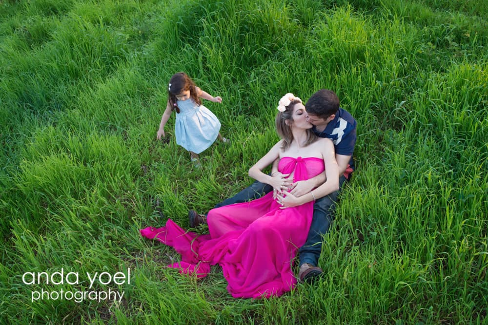 הריונית בשמלה סגולה עם בן זוגה וילדתם על הדשא בסשן צילומי הריון בטבע