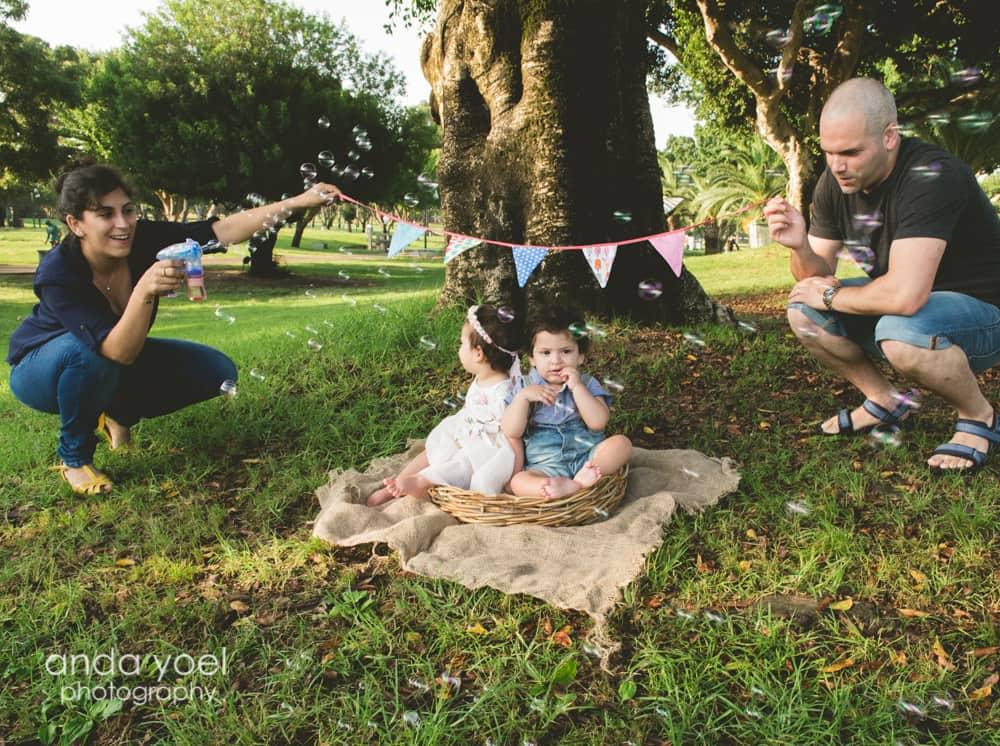 תאומים מחייכים על רקע דגלונים ובועות סבון בפארק - מסדרת צילומי תינוקות גיל שנה אנדה יואל