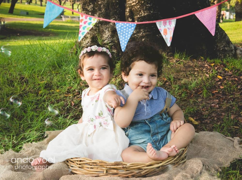תאומים בני שנה מחייכים על רקע דגלים צבעוניים בפארק - מסדרת צילומי תינוקות גיל שנה בטבע אנדה יואל
