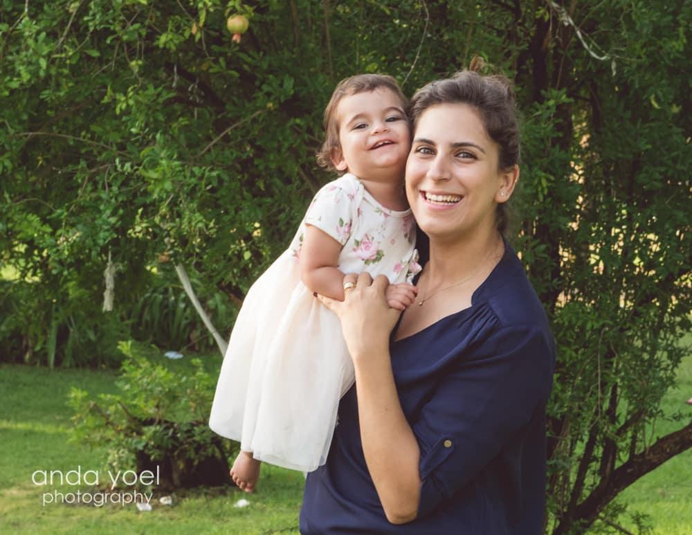 תינוקת חייכנית בידיים של אמא - מסדרת צילום תינוקות בטבע בגיל שנה - אנדה יואל