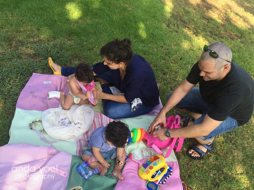 תינוקות תאומים בני שנה על שמיכה צבעונית בפארק - מסדרת צילום תינוקות גיל שנה אנדה יואל