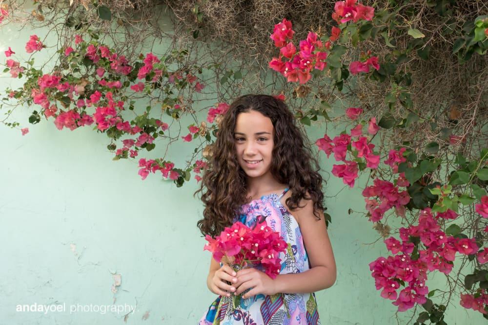 ילדת בת מצווה על רקע קיר תעלת ופרחים סגולים - אנדה יואל