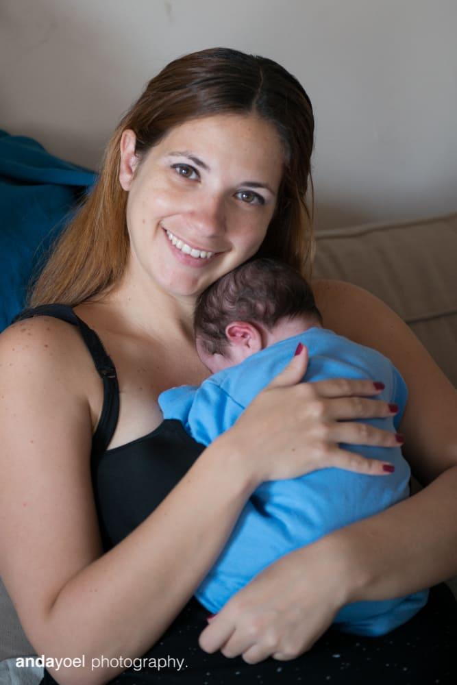 אמא מחבקת תינוקה הניובורן ומחייכת למצלמה בסדנת הצילום של אנדה יואל