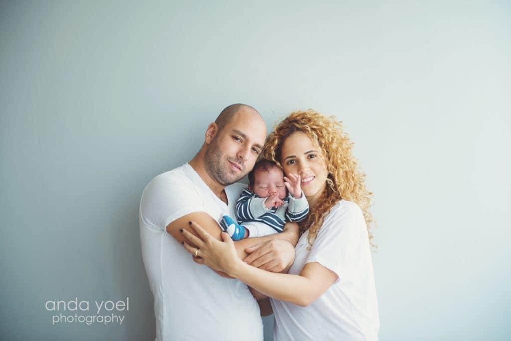 תינוק ניובורן בן שלושה שבועות בידיים של הוריו בצילומי ניובורן בסטודיו אנדה יואל