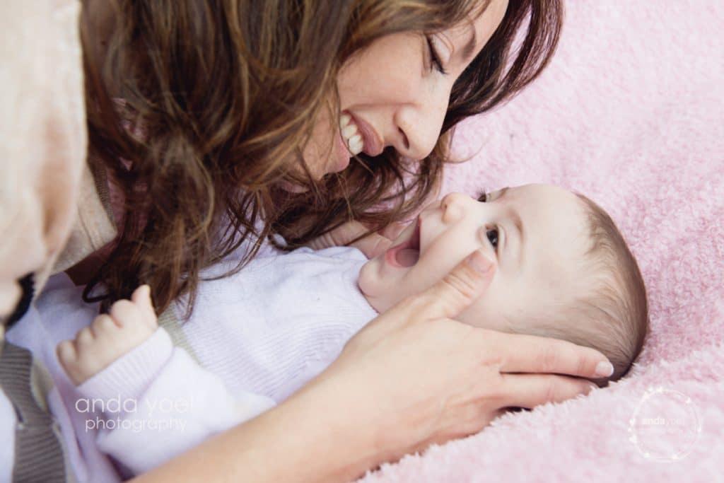 אמה רוכנת ומחייכת לתינקת שלה על רקע בד ורוד בסדנת צילום תינוקות בהנחיית אנדה יואל