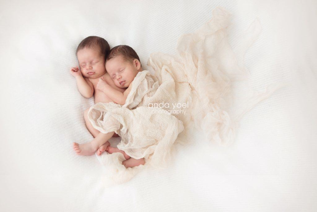 אחיות תינוקות תאומות נשענות אחת על השנייה על רקע לבן - מסדרת צילומי ניובורן תאומות, אנדה יואל