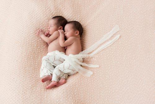 אחיות תינוקות תאומות עם מכנס לבן אחת ליד השנייה על רקע בד ורוד עם נקודות לבנות - מסדרת צילומי ניובורן תאומים, אנדה יואל