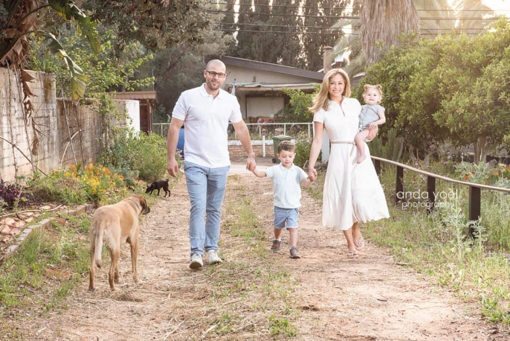 ליהיא גרינר עם בן הזוג יוסי, הילדים והכלב מחזיקים ידיים ומטייליים בכפר - מסדרת צילומי המשפחה בטבע אנדה יואל