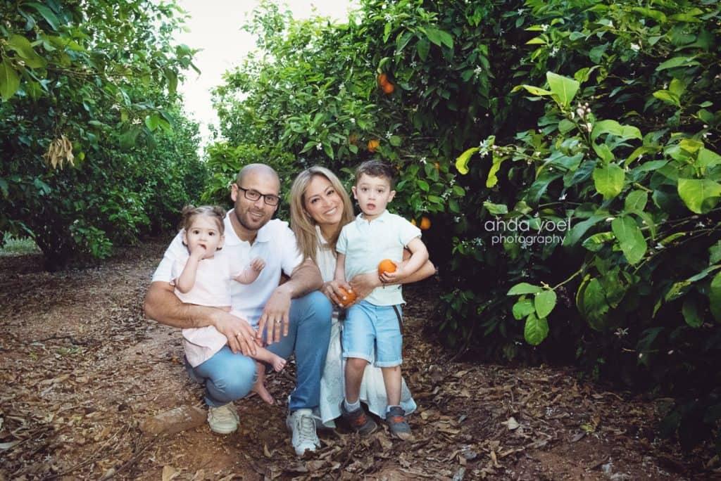 ליהיא גרינר וובני המשפחה מצטלמים בפרדס ומחזיקים קלמנטינות כתומות - מסדרת צילומי המשפחה בטבע אנדה יואל