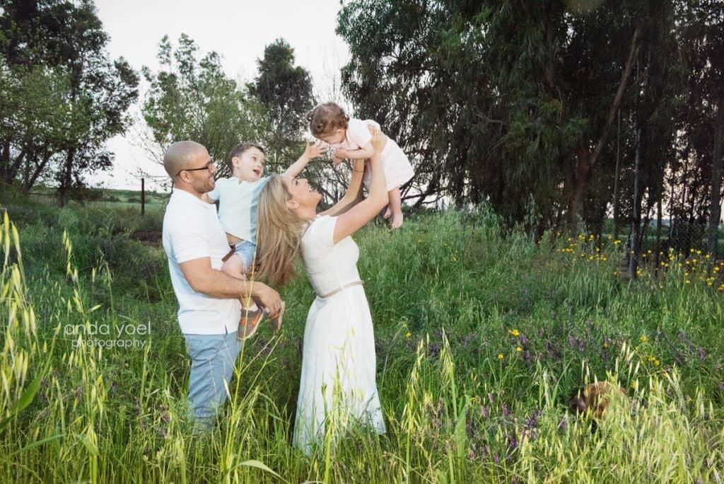 ליהיא גרינר מרימה את בתה ג'אולין האבא והאח מביטים עליה ומחייכים בשדה ירוק - מסדרת צילומי המשפחה בטבע אנדה יואל