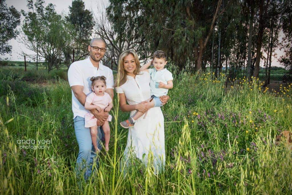 ליהיא גרינר מרימה את בנה בידיה, יוסי מחזיק את הבת בשדה ירוק בשקיעה - מסדרת צילומי המשפחה בטבע אנדה יואל
