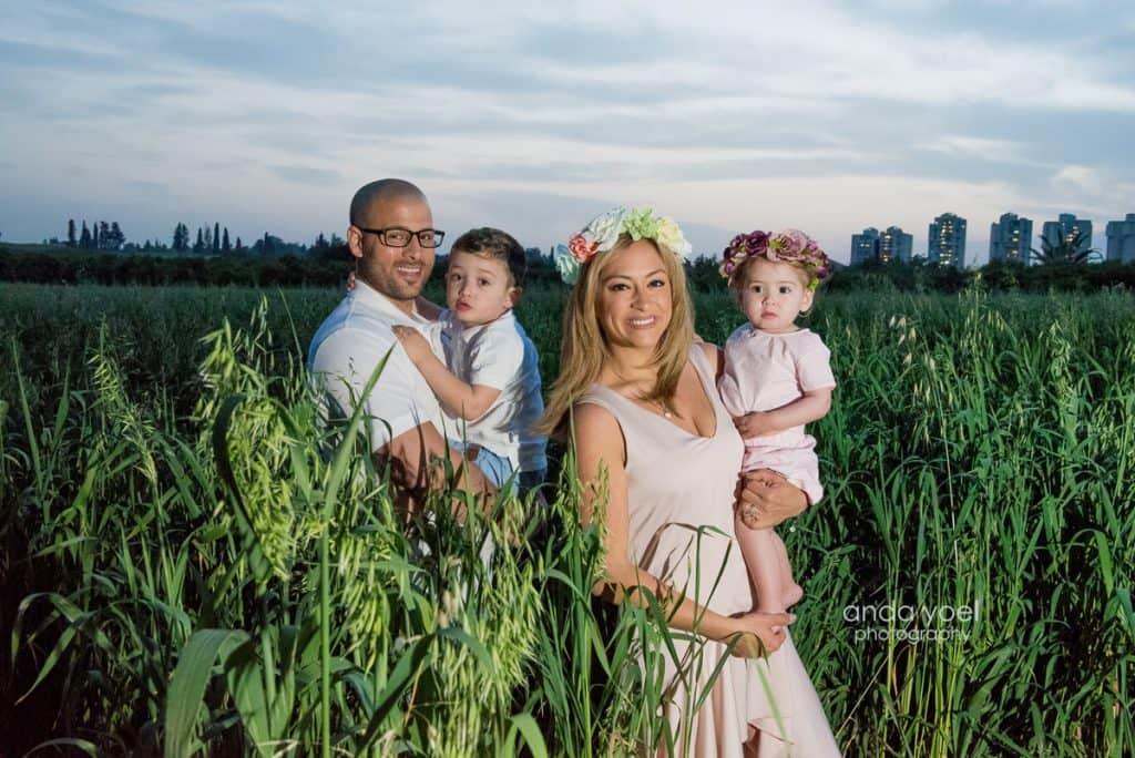 ליהיא גרינר ויוסי מחזיקים את ילדיהם בידיים שדה חיטה ירוק בשקיעה - מסדרת צילומי המשפחה בטבע אנדה יואל
