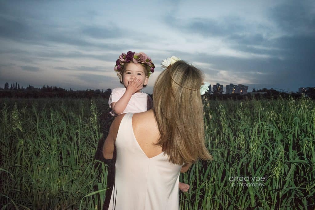 ליהיא גרינר בגבה למצלמה מחזיקה את בתה בידיים בשדה חיטה ירוק בשקיעה - מסדרת צילומי המשפחה בטבע אנדה יואל