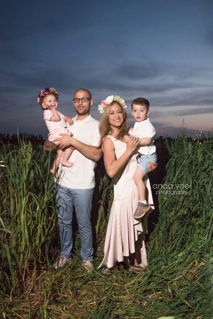 ליהיא גרינר ויוסי מחזיקים את הילדים בידיים בשדה חיטה ירוק בשקיעה - מסדרת צילומי המשפחה בטבע אנדה יואל