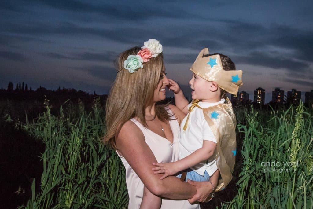 ליהיא גרינר עם זר על ראשה מחזיקה את בנה בידיים בשדה חיטה ירוק בשקיעה - מסדרת צילומי המשפחה בטבע אנדה יואל