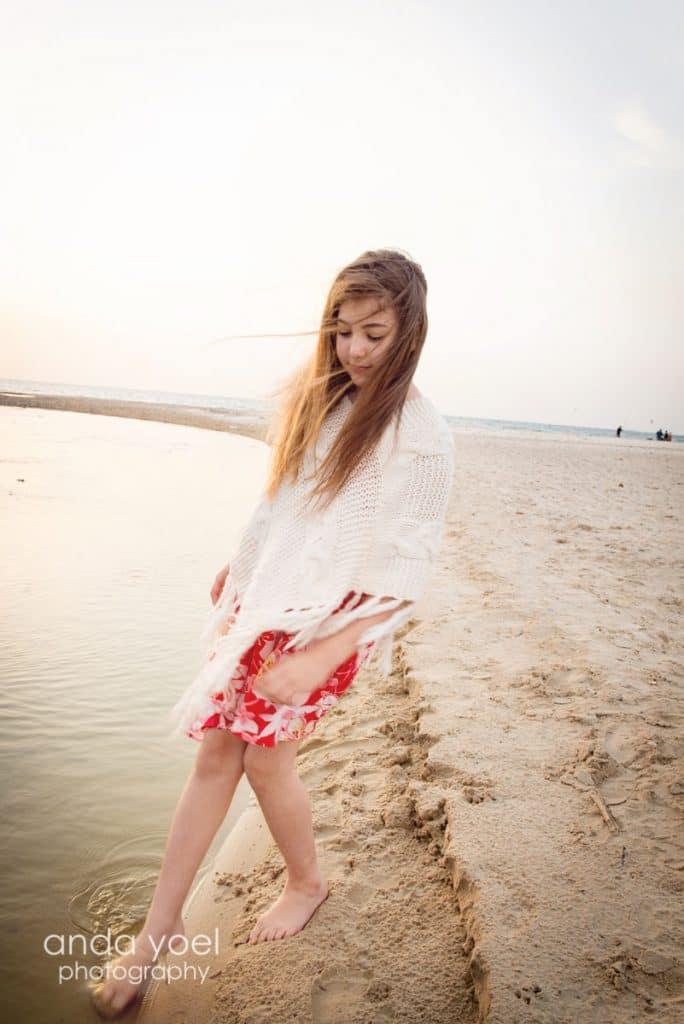 ילדת בת מצווה לובשת סווצ'ר לבן מכניסה רגל למים על רקע חוף הים מסדרת צילומי בוק בים אנדה יואל