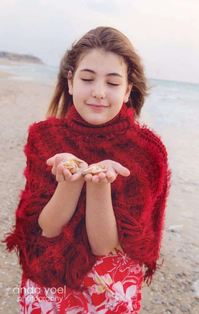 ילדת בת מצווה לובשת סווצ'ר אדום על רקע חוף הים מסדרת צילומי בוק בים אנדה יואל