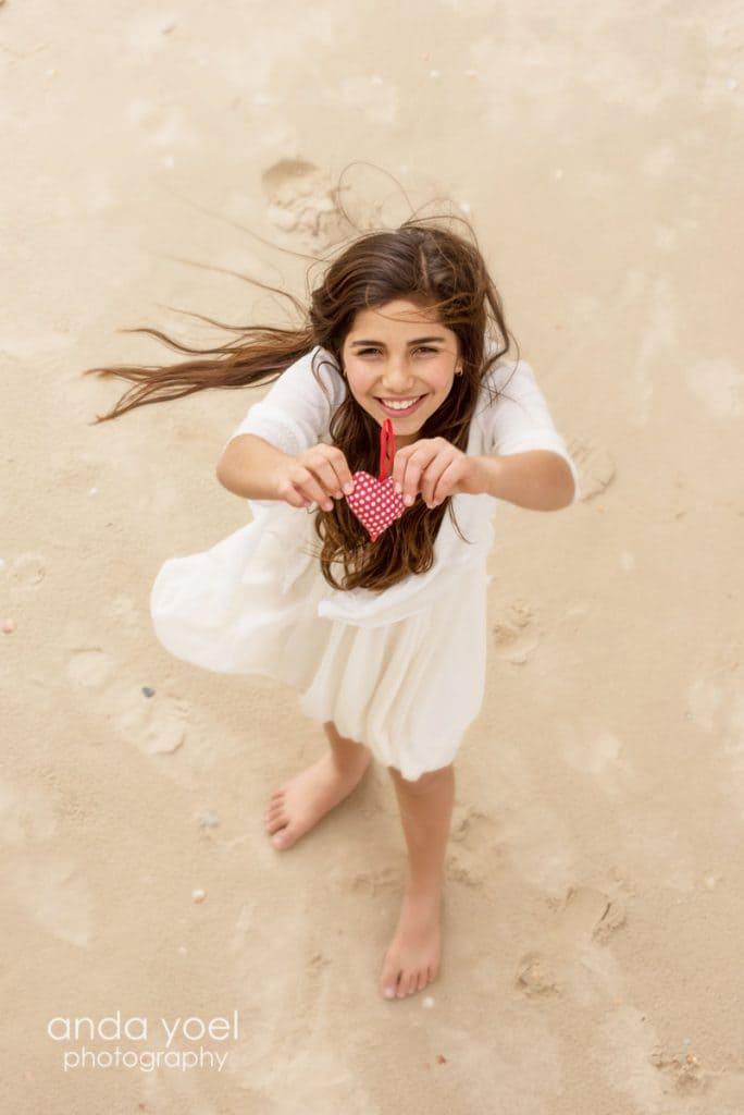 ילדת בת מצווה מחזיקה לב מנוקד מבד ומביטה למעלע - מתוך סדרת צילומי בוק בת מצווה בטבע - אנדה יואל