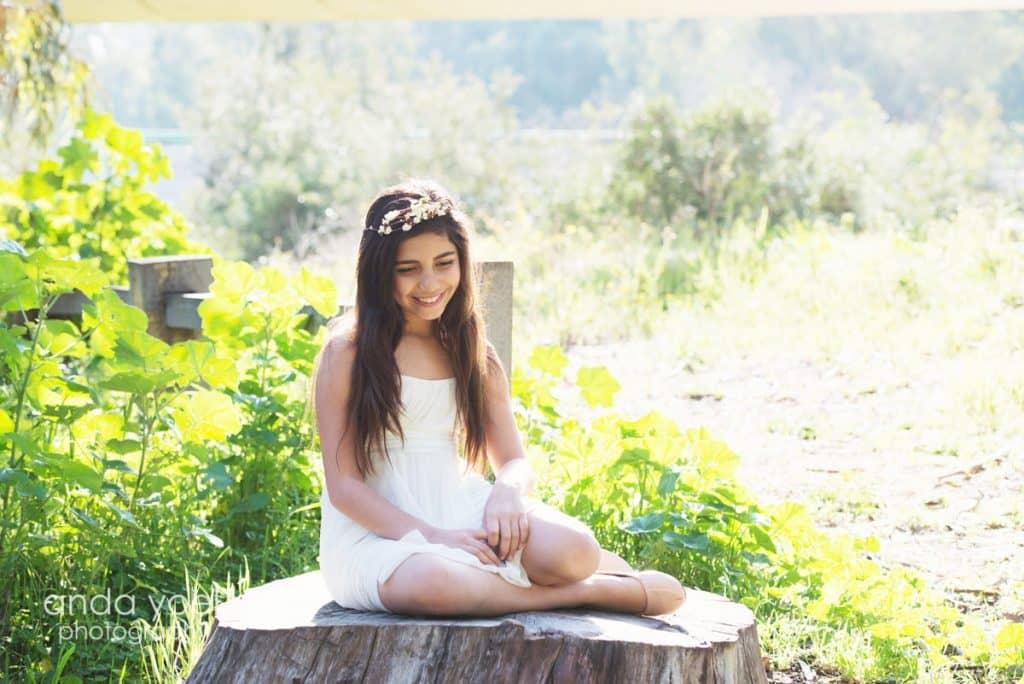 ילדת בת מצווה יושבת על גזע עץ ביער - מתוך סדרת צילומי בוק בת מצווה בטבע - אנדה יואל