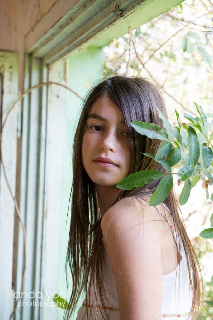 ילדת בת מצווהבתוך בית עץ מביטה למצלמה - מתוך סדרת צילומי בוק בת מצווה בטבע - אנדה יואל