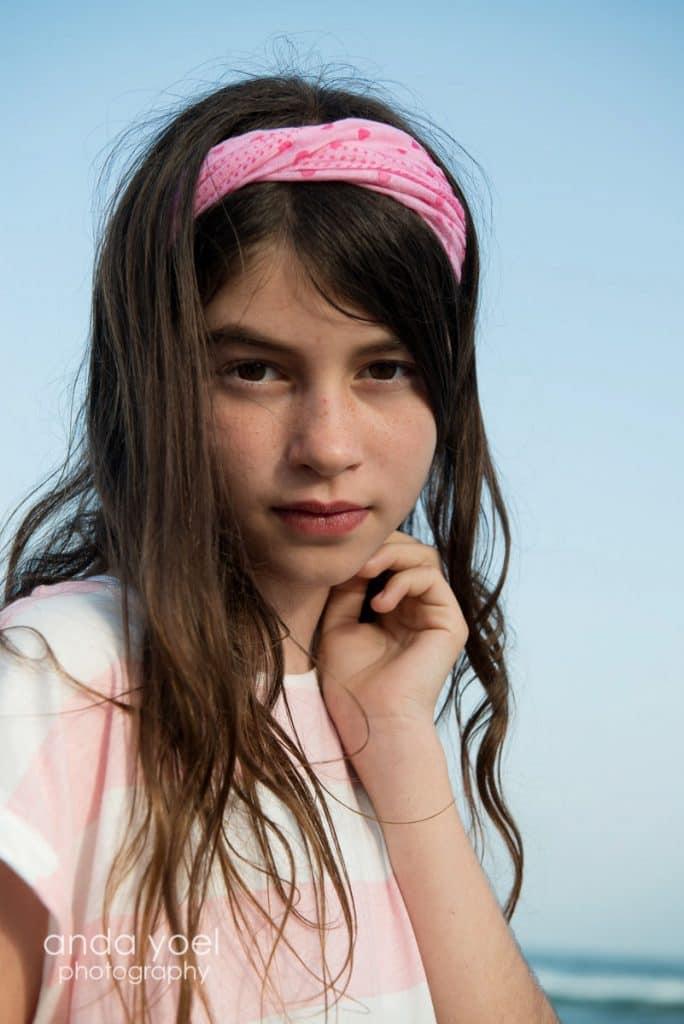 ילדת בת מצווה עם סדר ורוד מביטה למצלמה - מתוך סדרת צילומי בוק בת מצווה בים - אנדה יואל