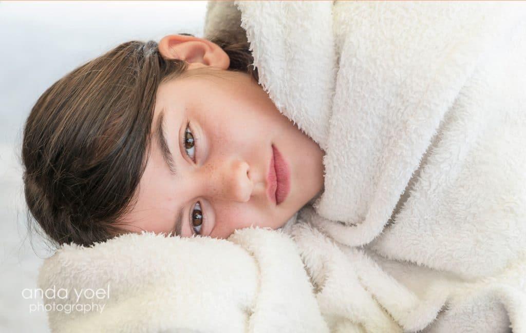 ילדת בת מצווה עם נמשים עטופה בשמיכה לבנה - מתוך סדרת צילומי בוק בת מצווה בים - אנדה יואל