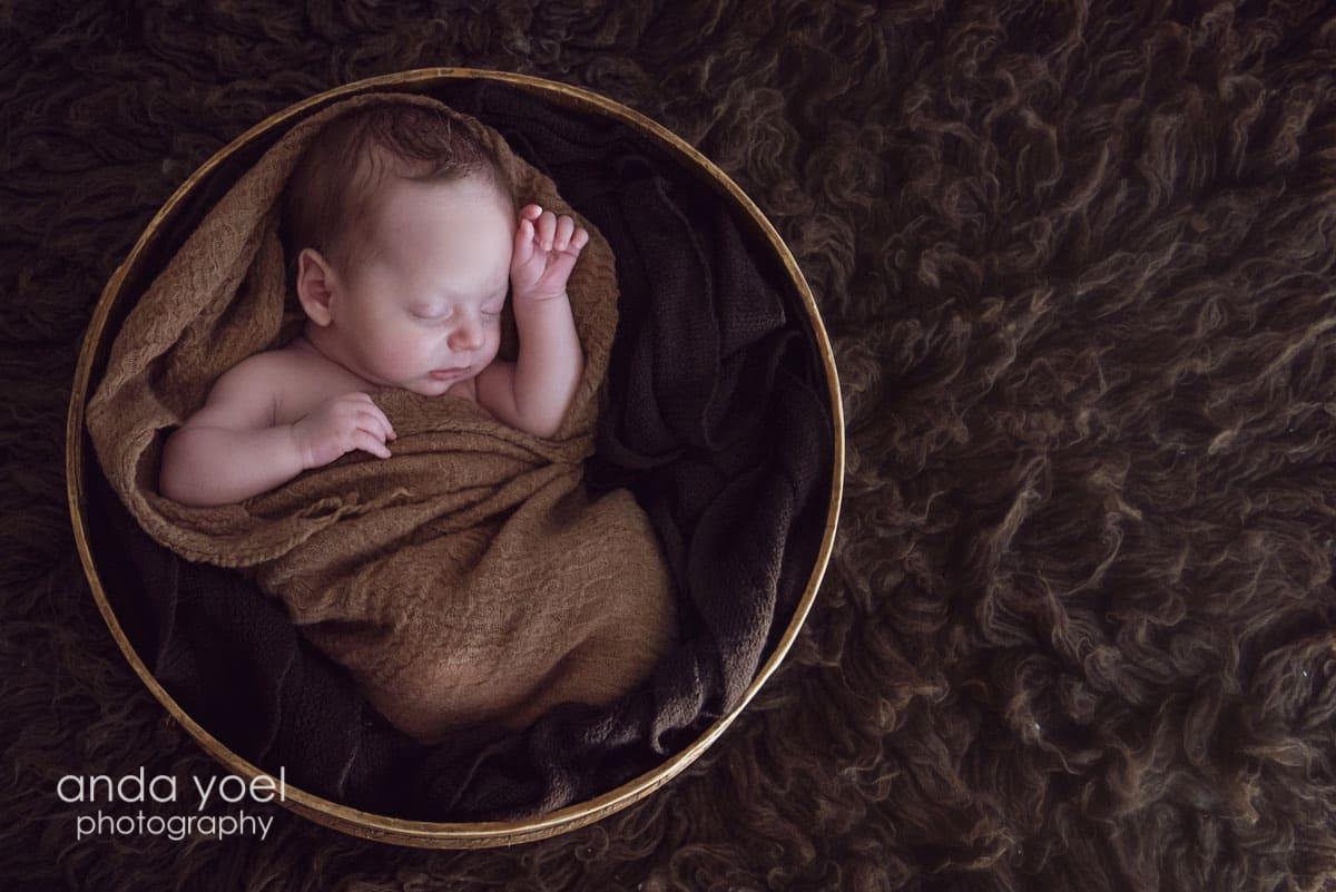 תינוק ניובורן בסלסלה עגולה - מתוך סדרת צילומי ניו בורן של אנדה יואל