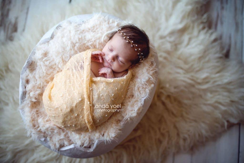 אנדה יואל צלמת ניובורן - תינוקת בעיטוף צהוב מנוקד בתוך קליפת ביצה