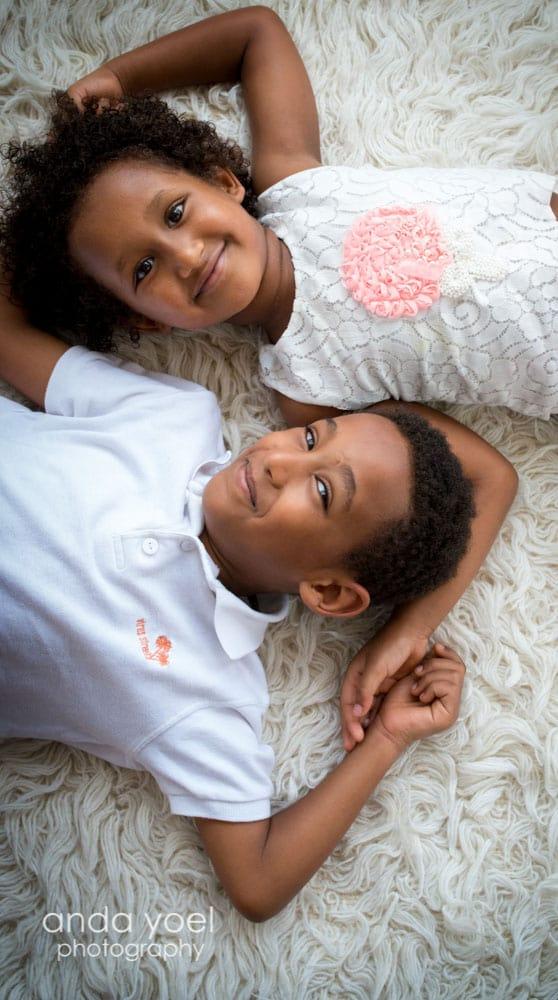 אדם ומזל על שטיח לבן מחזיקים ידיים ומחייכים למצלמה - צילומי ילדים ומשפחה אנדה יואל