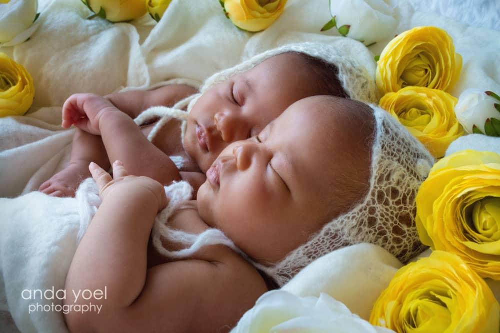 מרים ומרתה ישנות על רקע לבן ופרחים צהובים ולראשן כובע לבן - צילומי ילדים ומשפחה אנדה יואל