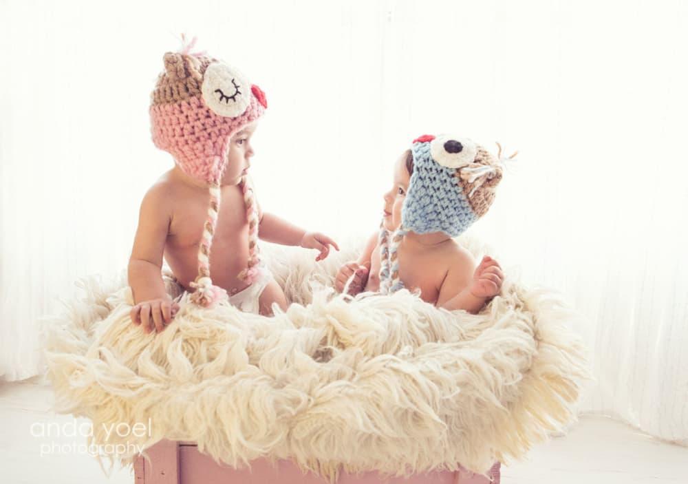 תאומות בנות שנה עם כובע ינשוף בצילומי גיל שנה בסטודיו, אנדה יואל