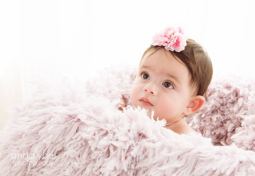 תינוקת עם פרח בשיער בצילומי גיל שנה בסטודיו, אנדה יואל