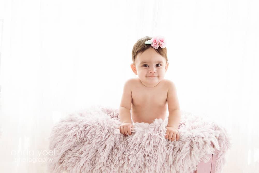 תינוקת בתוך ארגז ורוד בצילומי גיל שנה בסטודיו, אנדה יואל