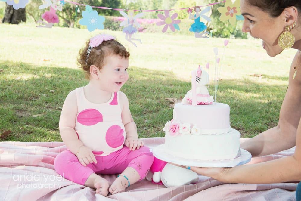 תינוקת בת שנה עם עוגת יום הולדת בצילומי גיל שנה בטבע מסדרת הצילומים של אנדה יואל