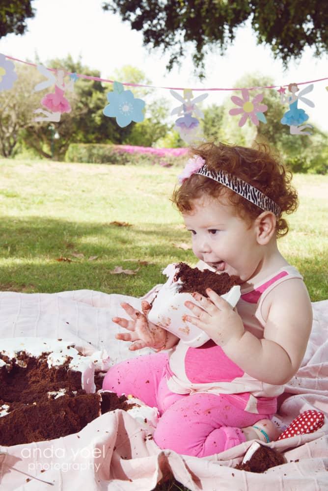 תינוקת בת שנה טועמת עוגת יום הולדת בצילומי גיל שנה בטבע מסדרת הצילומים של אנדה יואל