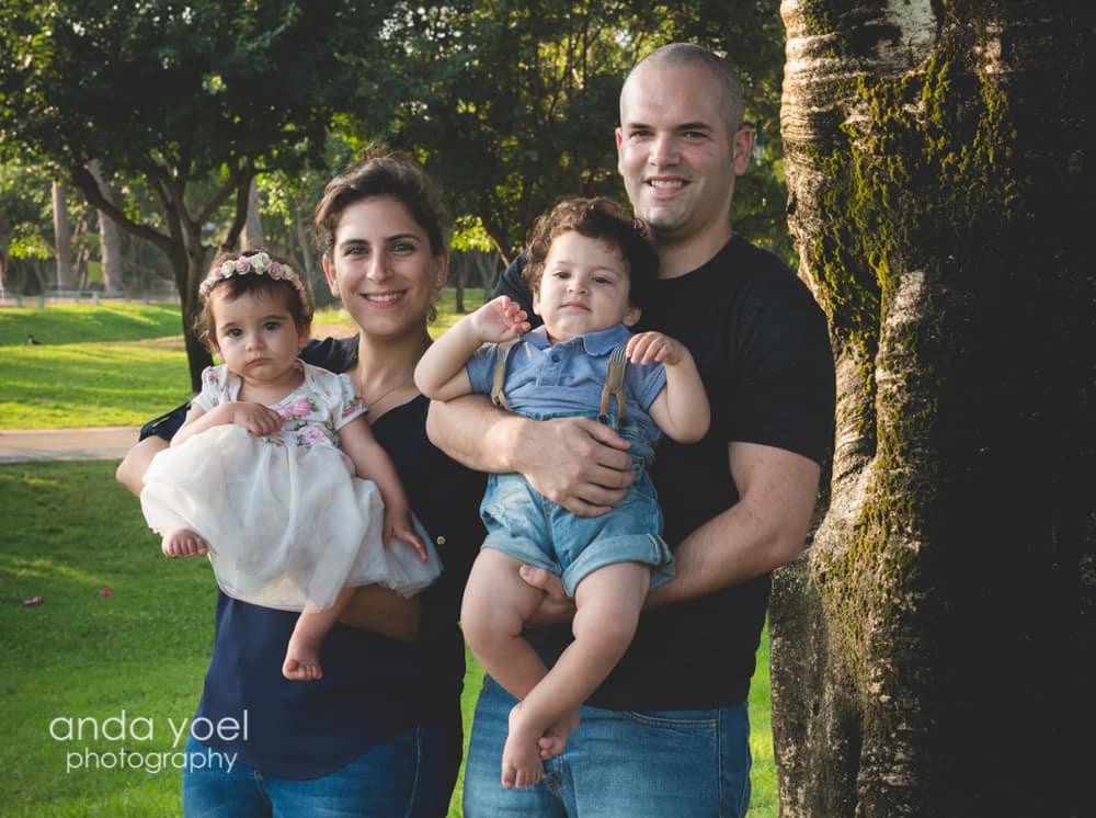 תאומים בן ובת בני שנה בידיים של ההורים בצילומי גיל שנה בטבע מסדרת הצילומים של אנדה יואל