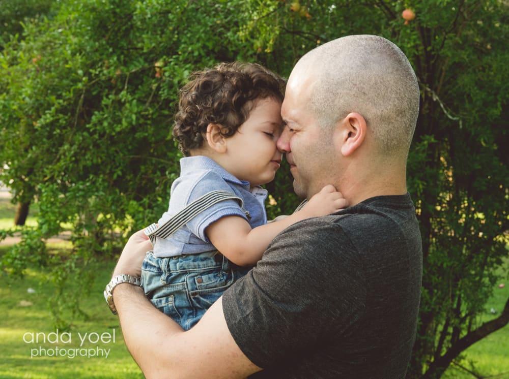 תינוק בן שנה בידיים של אבא מסדרת הצילומים של אנדה יואל