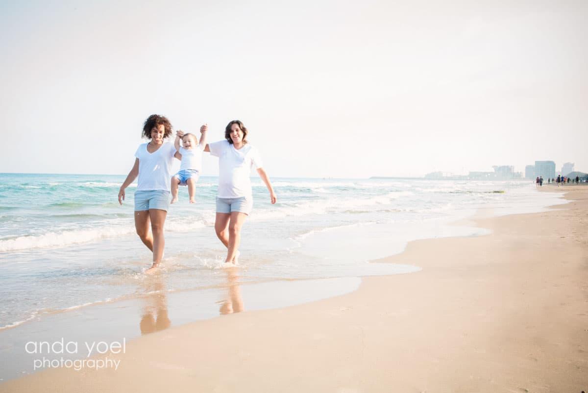 2 אמהות מרימות את ילדן בחוף, אחת מהן בהריון ורקע הזריחה מסדרת צילומי ההריון של אנדה יואל