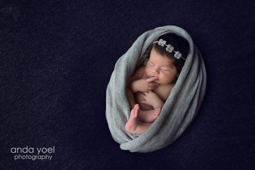 תינוקת בעיטוף אפור וסרט פרחוני - צילומי ניו בורן בסטודיו אנדה יואל