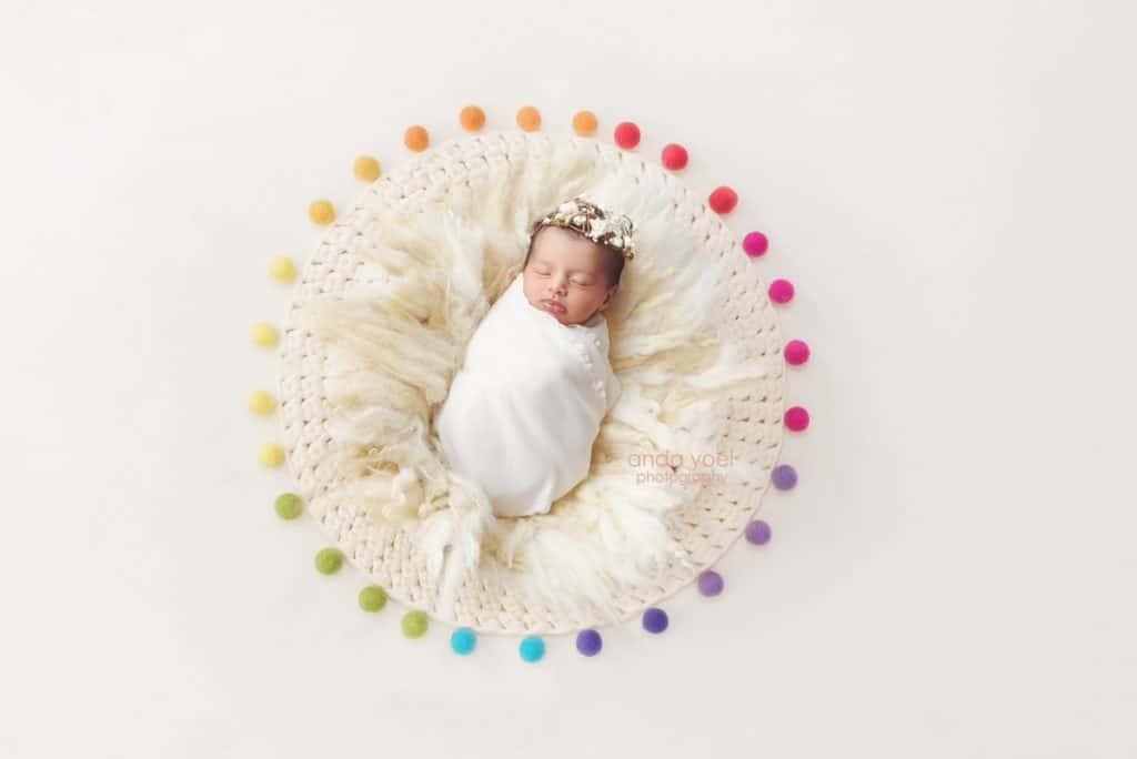 ניובורן בעיטוף לבן בין כדורי צמר צבעוניים - צילומי ניובורן בסטודיו אנדה יואל