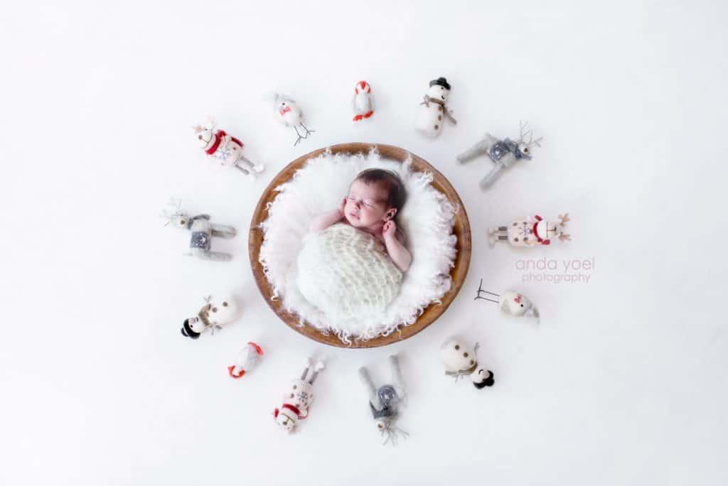 """תינוקת ניובורן בסלסלת עץ על רקע """"מושלג"""" (תמונה בעיבוד מורכב) אנדה יואל"""