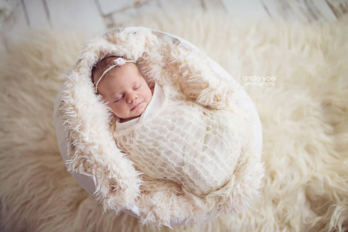 """צילומי ניובורן תינוקת עטופה לבן בתוך """"ביצה"""" לבנה - סטודיו אנדה יואל"""