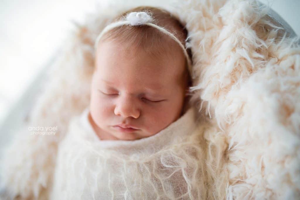 צילומי ניובורן תינוקת עטופה לבן וסרט לבן בשערה - סטודיו אנדה יואל