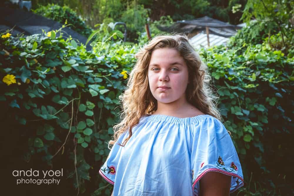 ילדה מביטה למצלמה על רקע צמחיה ירוקה בצילומי בוק בת מצווה - אנדה יואל
