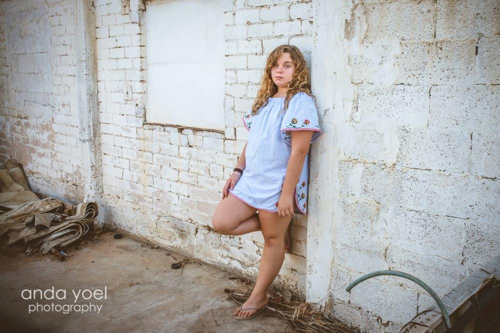 ילדה נשענת על קיר לבנים בצילומי בוק בת מצווה - אנדה יואל