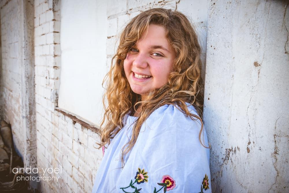 ילדה נשענת על קיר לבן בחיוך גדול בצילומי בוק בת מצווה - אנדה יואל