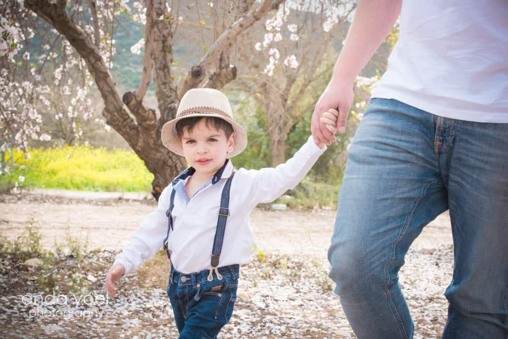 צילומי הריון ומשפחה בטבע במטע שקדיות ילד נותן יד לאבא - אנדה יואל